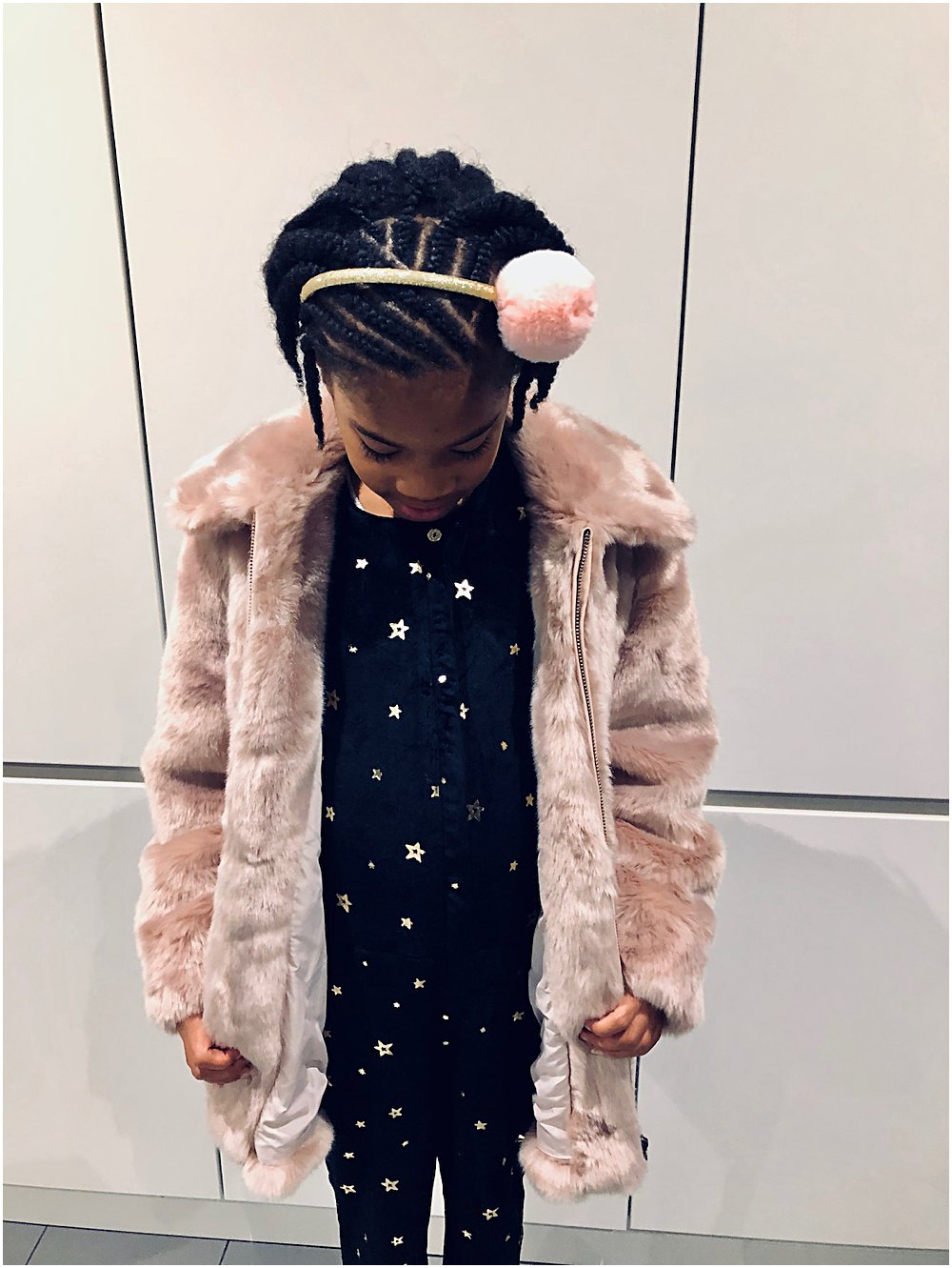 Little black girl in a faux fur pink coat and velvet star jumpsuit