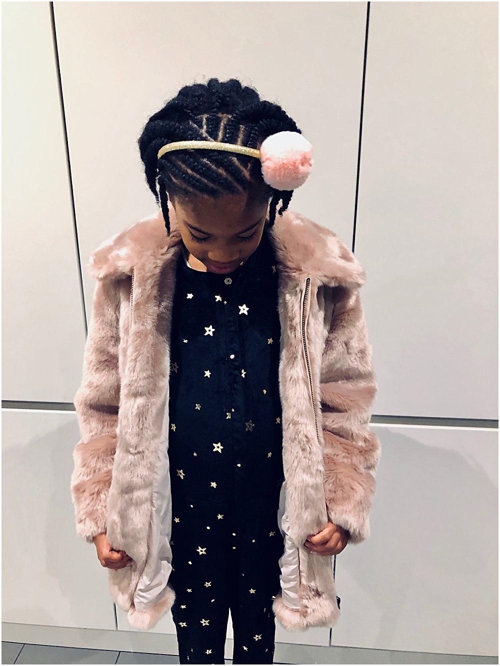 Little black girl in a faux fur pink coat and velvet star jumpsuit