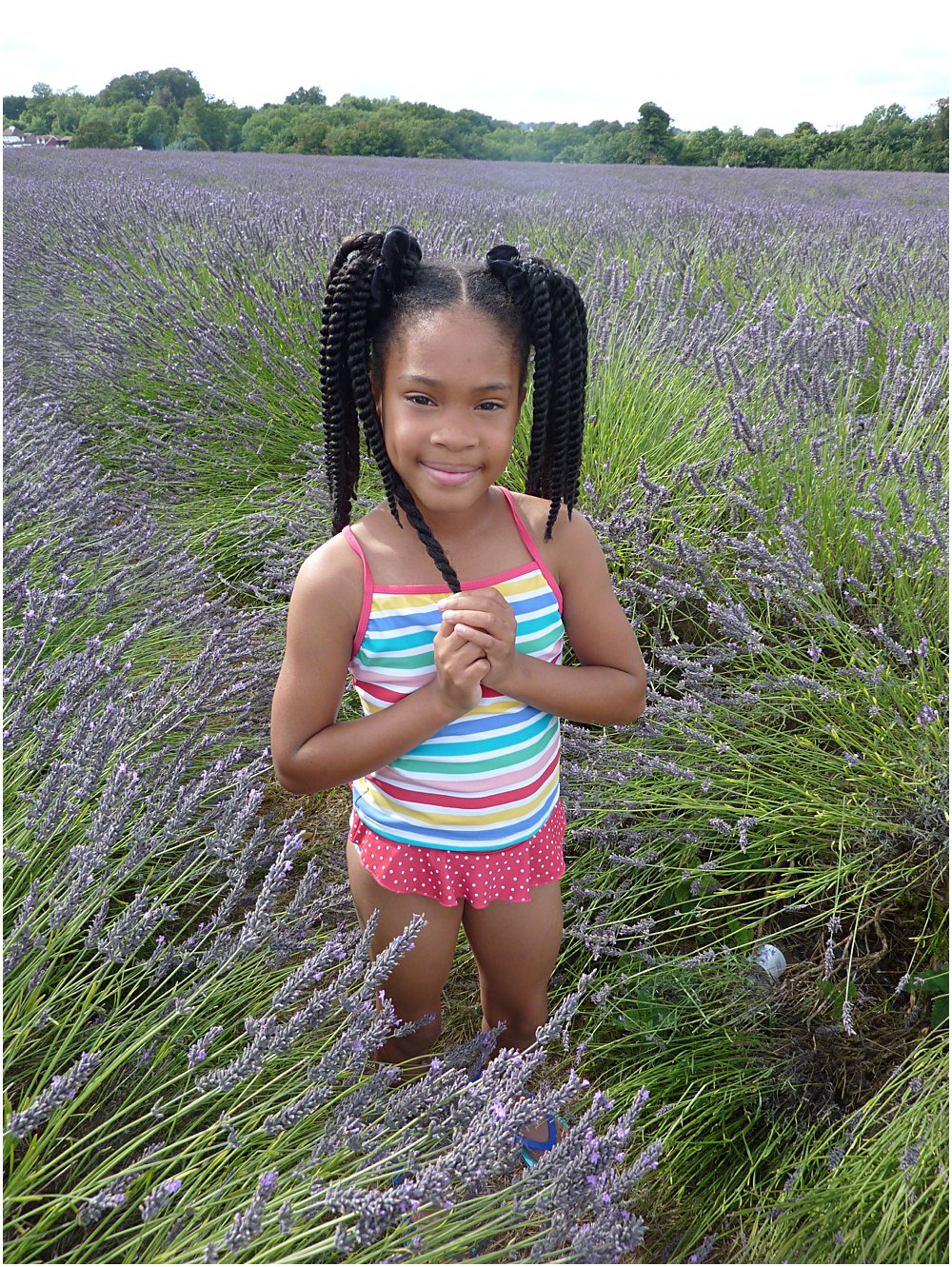 Little black girl in a lavender field wearing key trend for the SS18 season rainbow stripe swim suit.