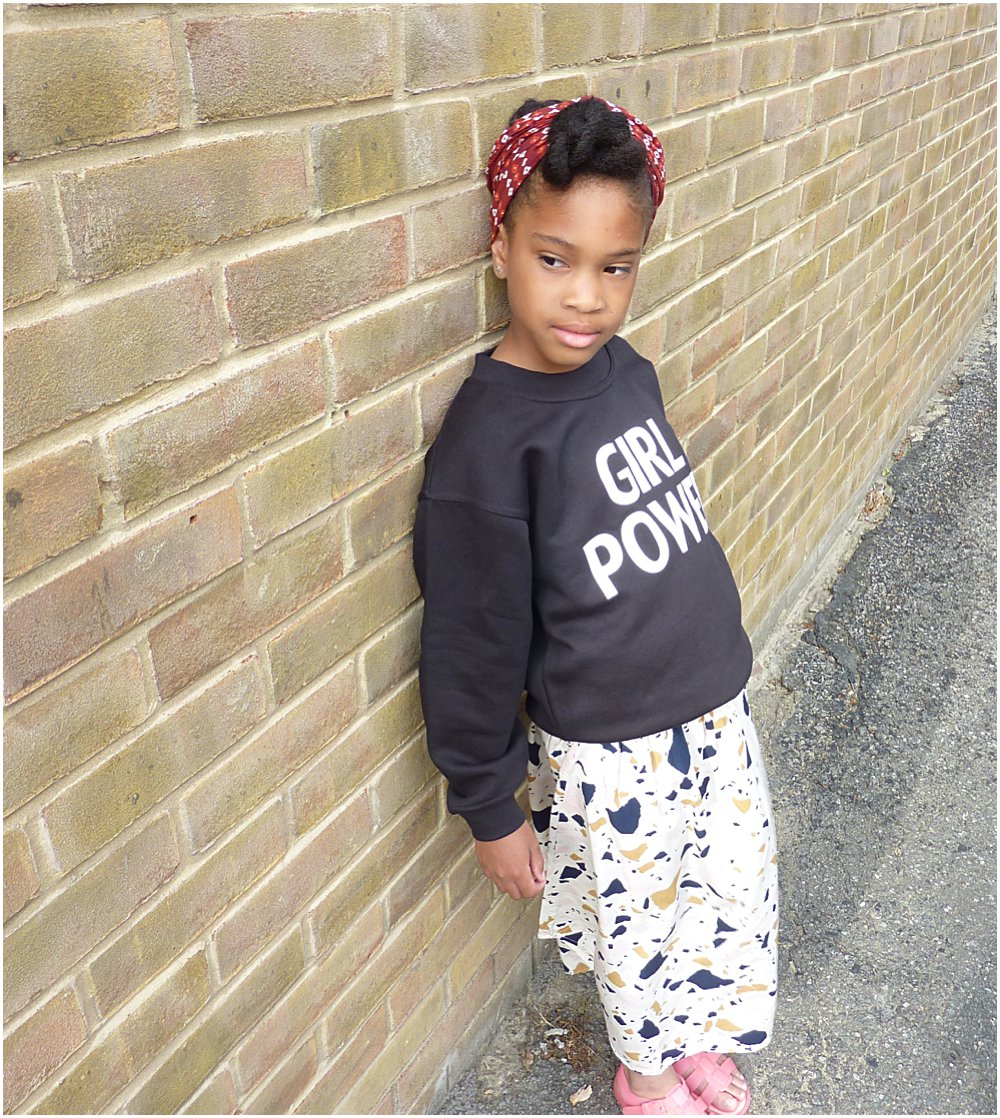 Little black girl wearing enpowering Girl Power slogan sweater from a collaboration with Lux and Black and Mini Edit