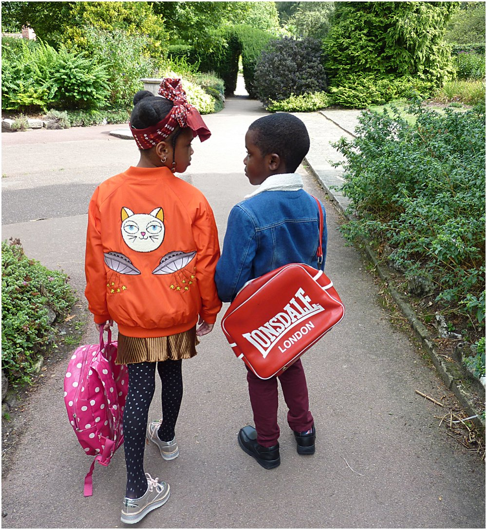 A little black boy and girl head off to school showing their new jackets for the coming AW18 season.