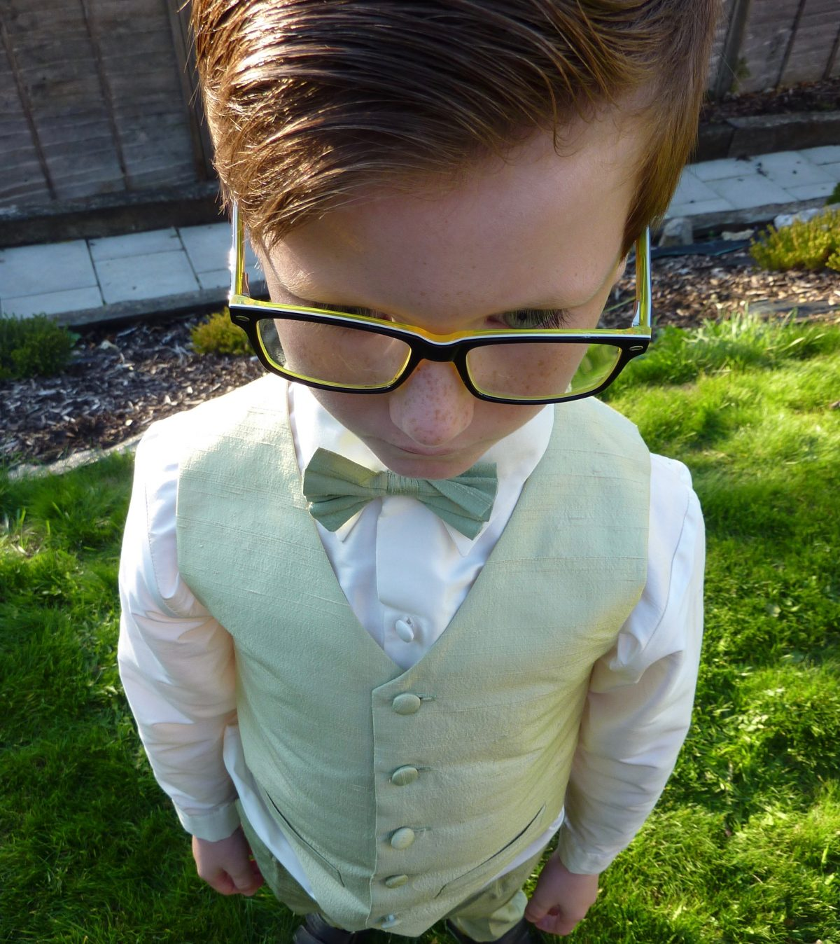 Little boy suited and booted in Little Bevan bow tie, shirt and trousers
