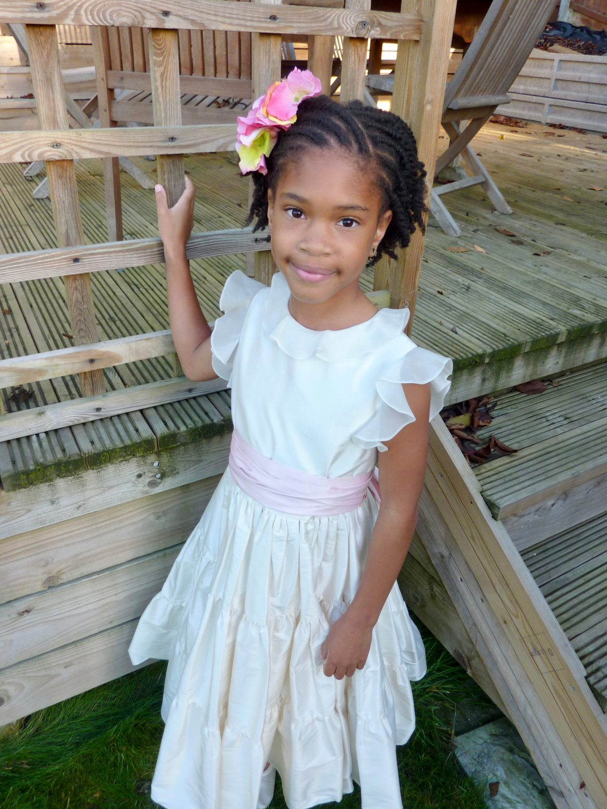 Little black girl wearing Little Bevan Olivia dress with pink sash