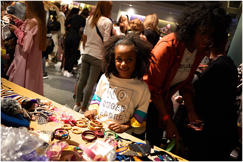 Little black girl in Hugland outfit enjoying all the accessories at Mini Mode, London't Premier Kids Fashion Show