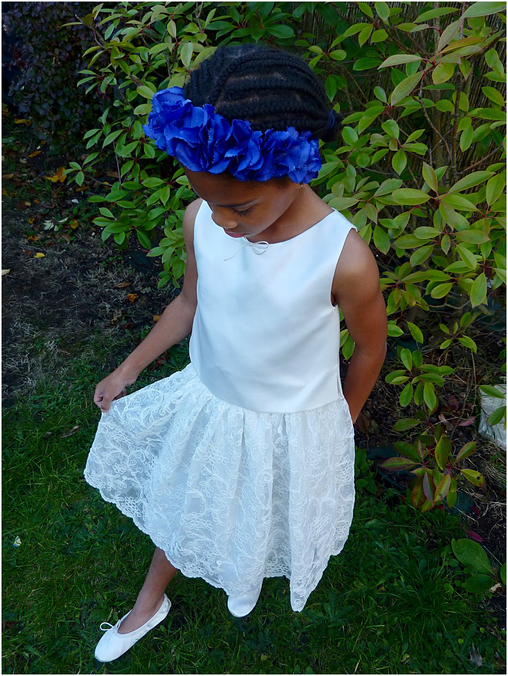 Little black girl smiling at wearing a gorgeous lace party dress by Little Bevan and head band by Clea Broad